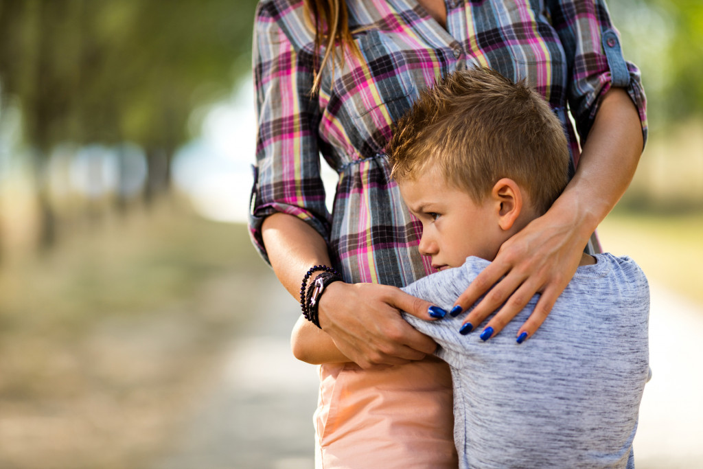 Anxious little boy at the park embracing his unrecognizable mother.