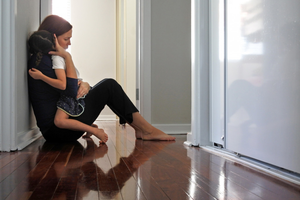 Sad mother hugging her young daughter on home corridor floor.