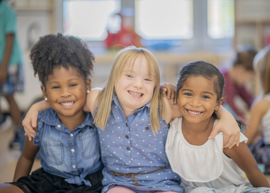 Three little girls of different ethnicities and abilities smile and put their arms around each other in a kindergarten classroom.