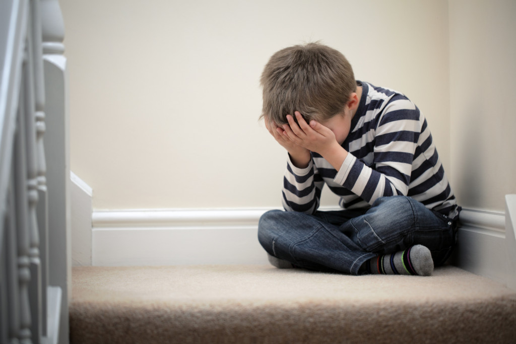 Upset child with head in hands sitting on staircase.