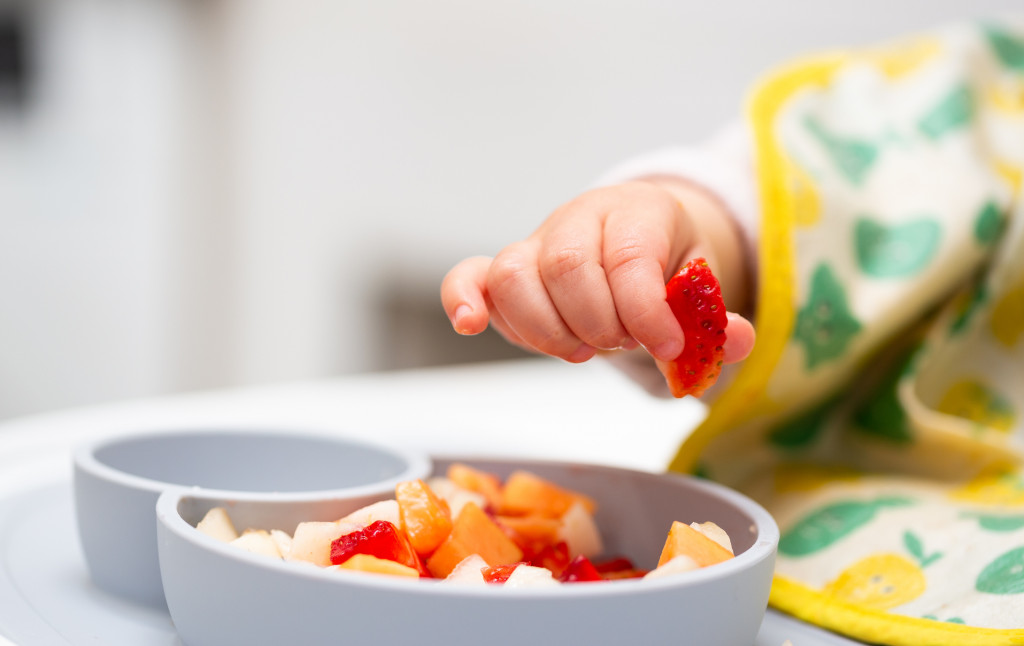 Macro Close up of Baby Hand with a Piece of Fruits Sitting in Child's Chair Kid Eating Healthy Food