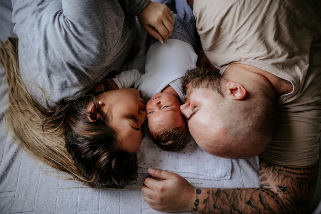 Family with one child laying on bed, enjoying day at home