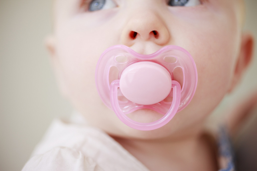 Close up photo of a little girl sucking a pink pacifier.