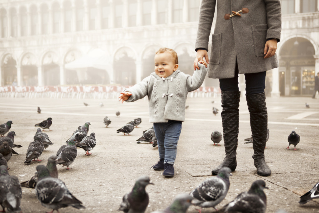 Boy playing with pigeons in Venice