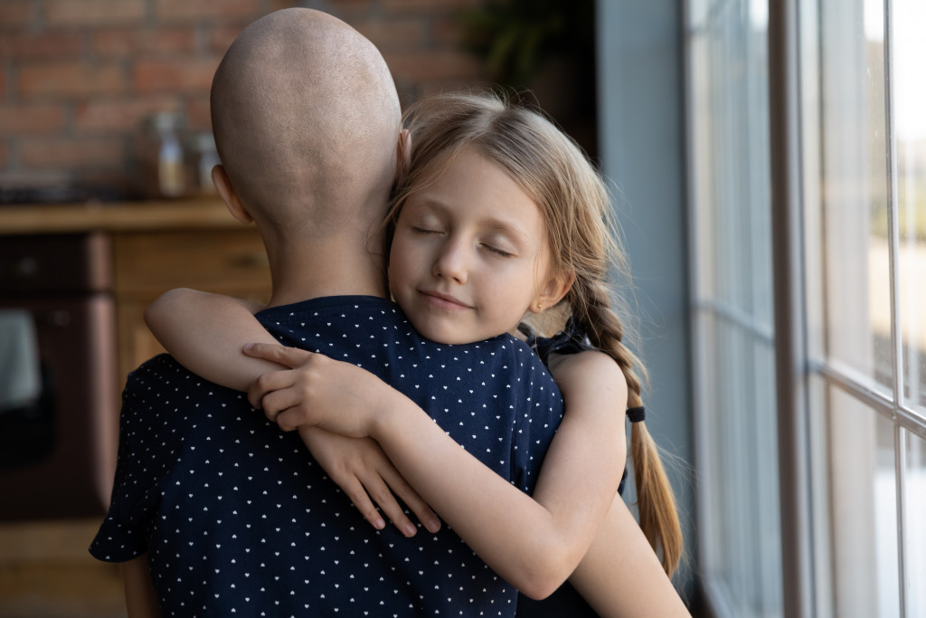 Caring daughter hugging her mother who is battling cancer.