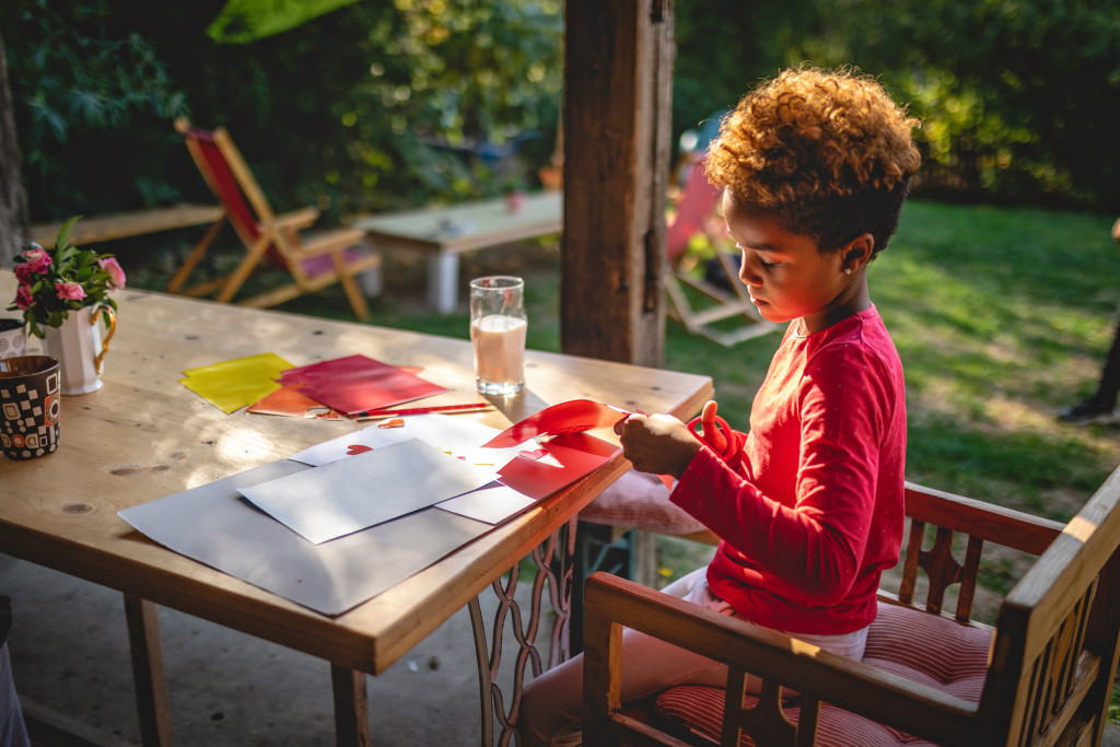 child doing art project homework on back porch.