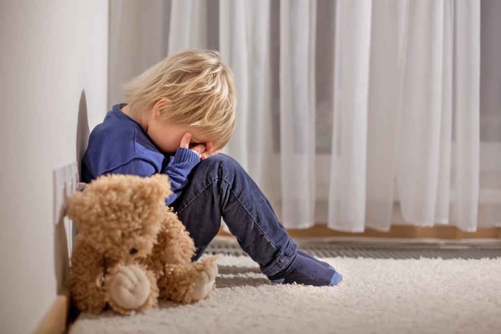 Sad little toddler child, blond boy, sitting in corner with teddy bear, punished for mischief