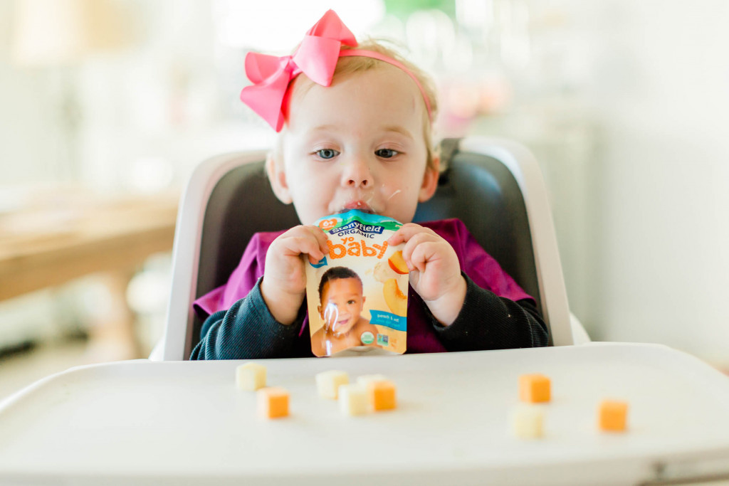 Baby girl eating a Stonyfield Yobaby pouch while sitting in her highchair with cubes of cheese on her tray.
