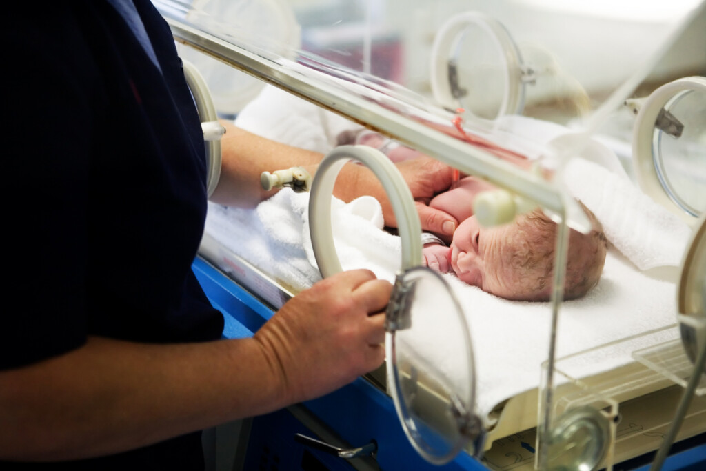 Nurse attends to a newborn baby girl in a hospital incubator.