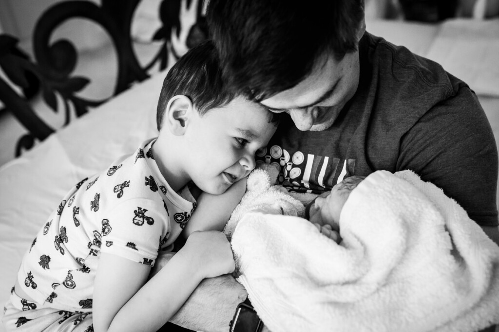 Big brother looking fondly down at his new baby sister that his dad is holding.