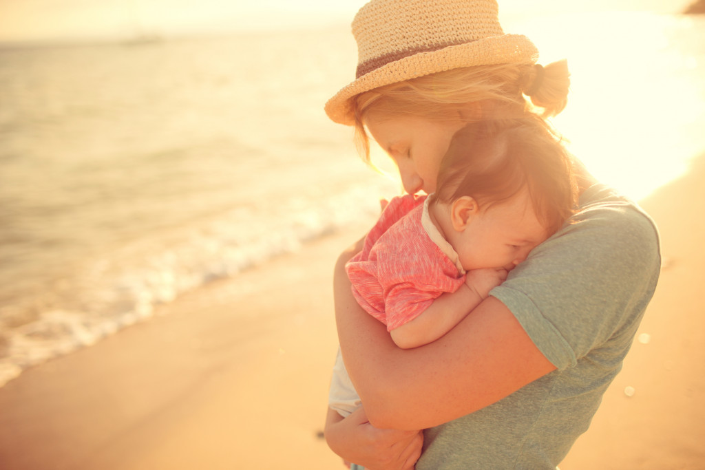 Mother and son gently hugging by the sea