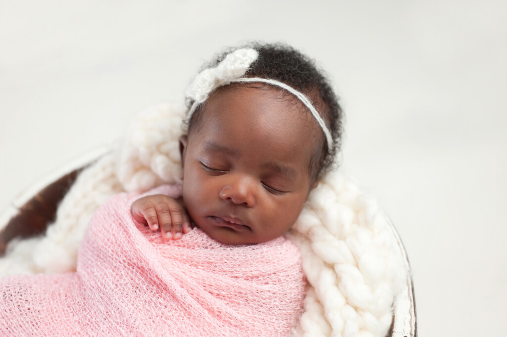 Portrait of a one month old, sleeping, newborn, baby girl. She is swaddled in pink and sleeping in a tiny bucket.