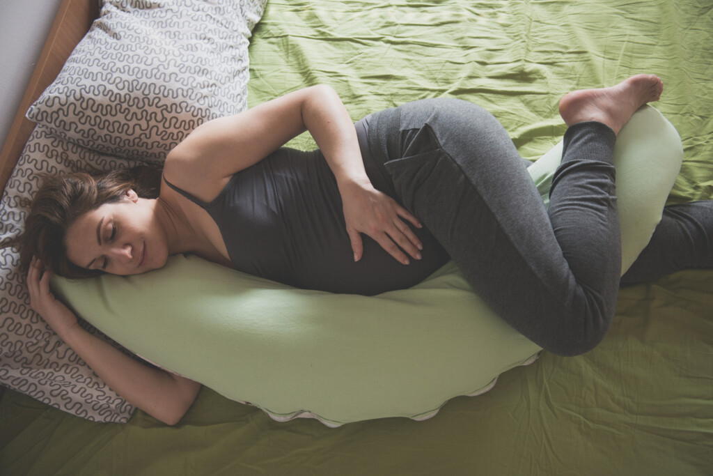 Pregnant woman feeling pain in abdomen while laying down with her pregnancy pillow.