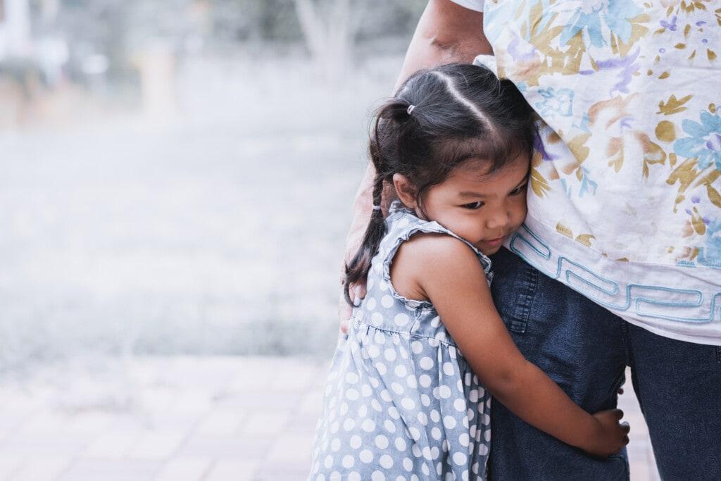 Sad asian little girl hugging her mother leg in vintage color tone