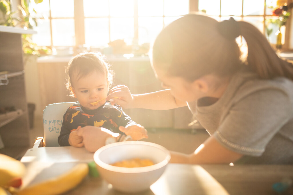Teenage girl feeding baby boy with solid food indoors,baby sitting in a high chair