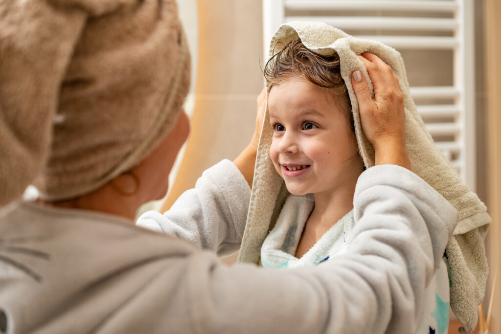 Close up mother is drying son head with towel