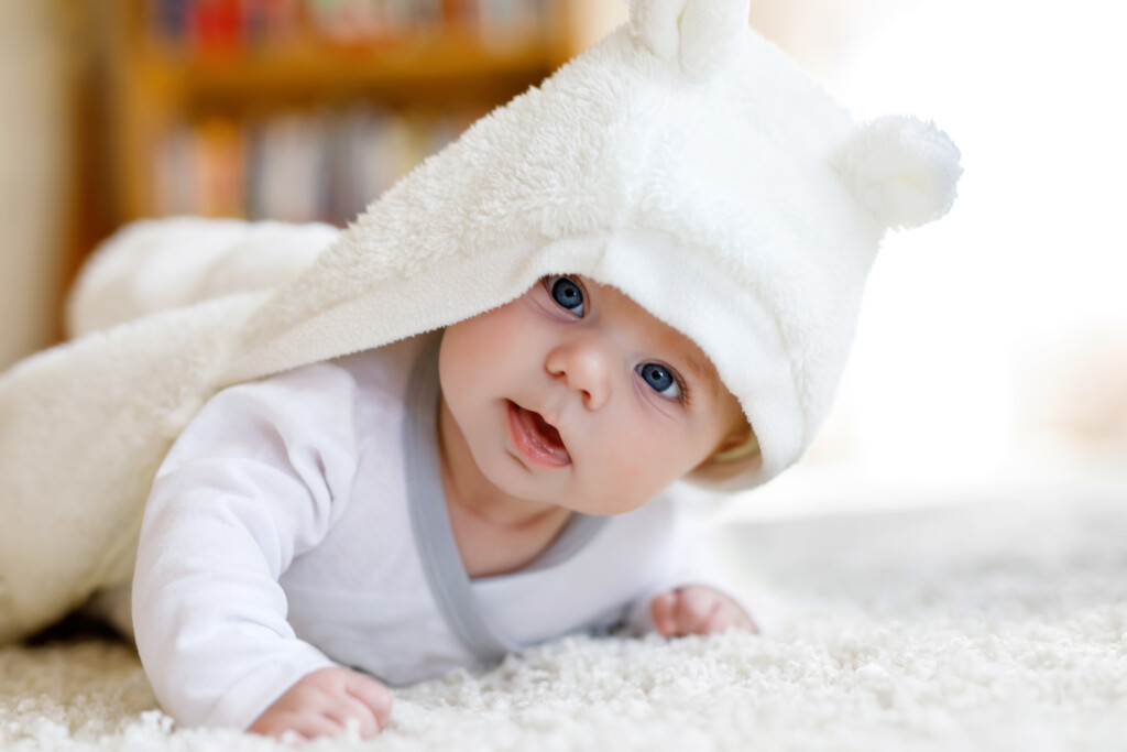 Baby boy with blue eyes wearing white towel or winter overall in white sunny bedroom.