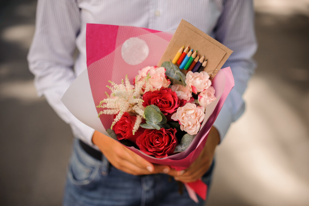 Boy dressed in a white shirt holding a festive bouquet decorated with a box of colorful pencils
