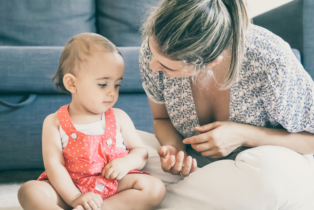 Happy little girl listening mom and sitting on carpet barefoot. Blonde mother sitting cross-legged and talking to daughter.