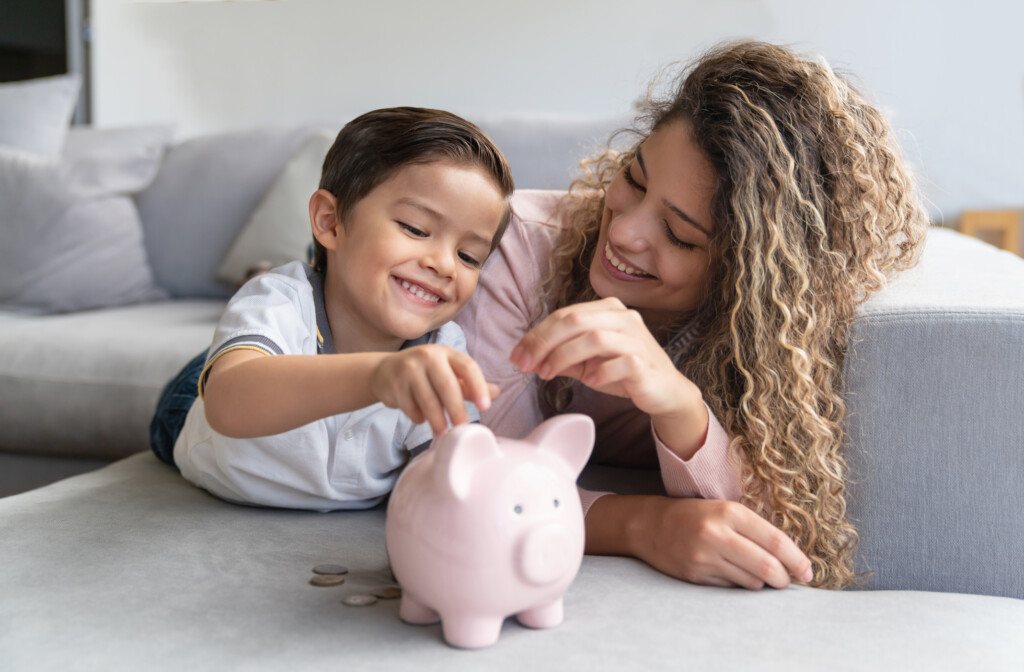 Portrait of a happy mother and son saving money in a piggybank and smiling