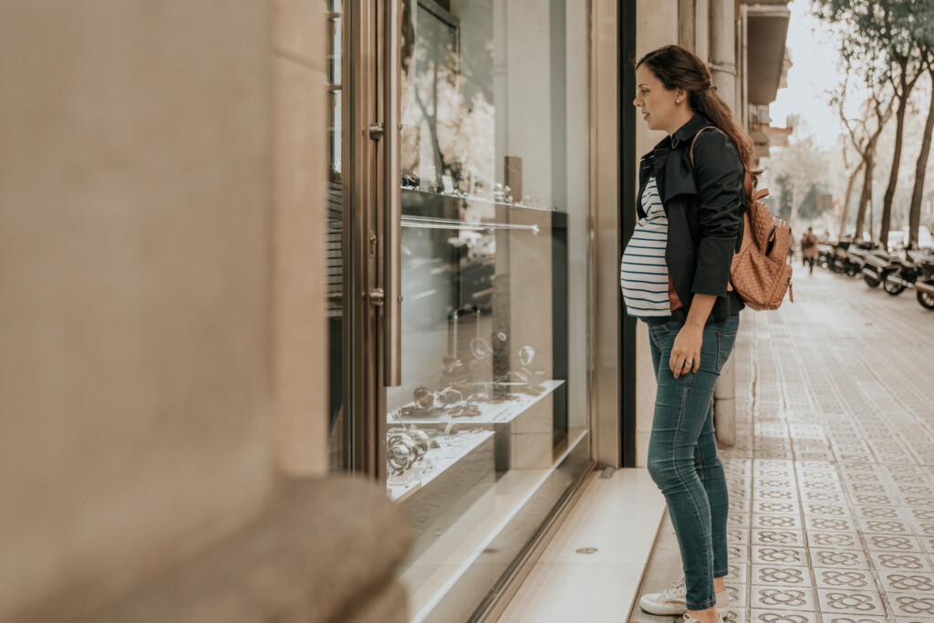 Pregnant woman window shopping at jewelry store