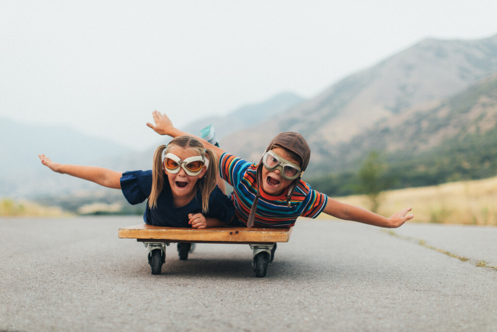 Two young children, a boy and a girl, are imagining flying into the sky while riding on a press cart. They have their arms spread out like wings and ready to use imagination in being like an airplane and piloting the airplane into the sky. They are wearing flying goggles on a rural road in Utah, USA.