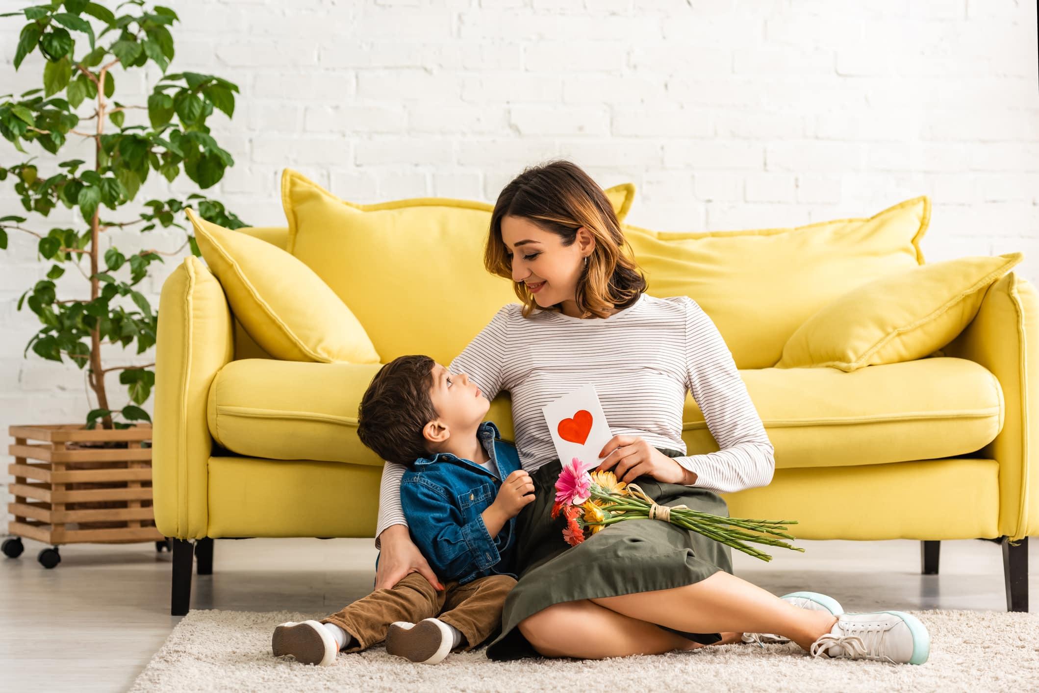 gülümseyen kadın, anneler günü kartı ve çiçeklerle katta otururken sevimli oğluna bakıyor