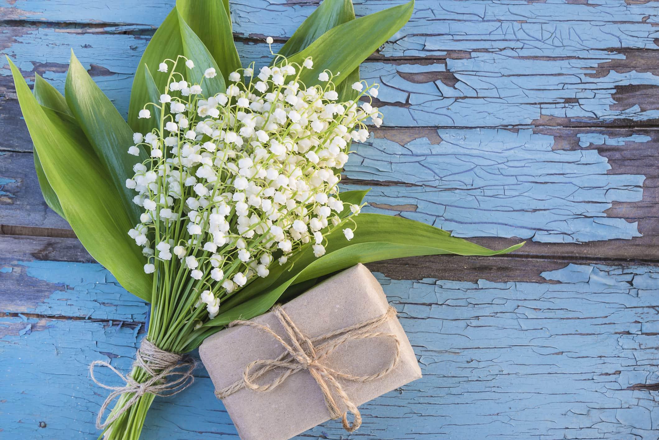 Vadideki zambak buketi ve mavi eski boya ahşap arka plan üzerinde el yapımı hediye kutusu.