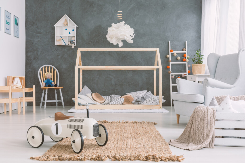 Baby room in scandinavian style with armchair and wood bed