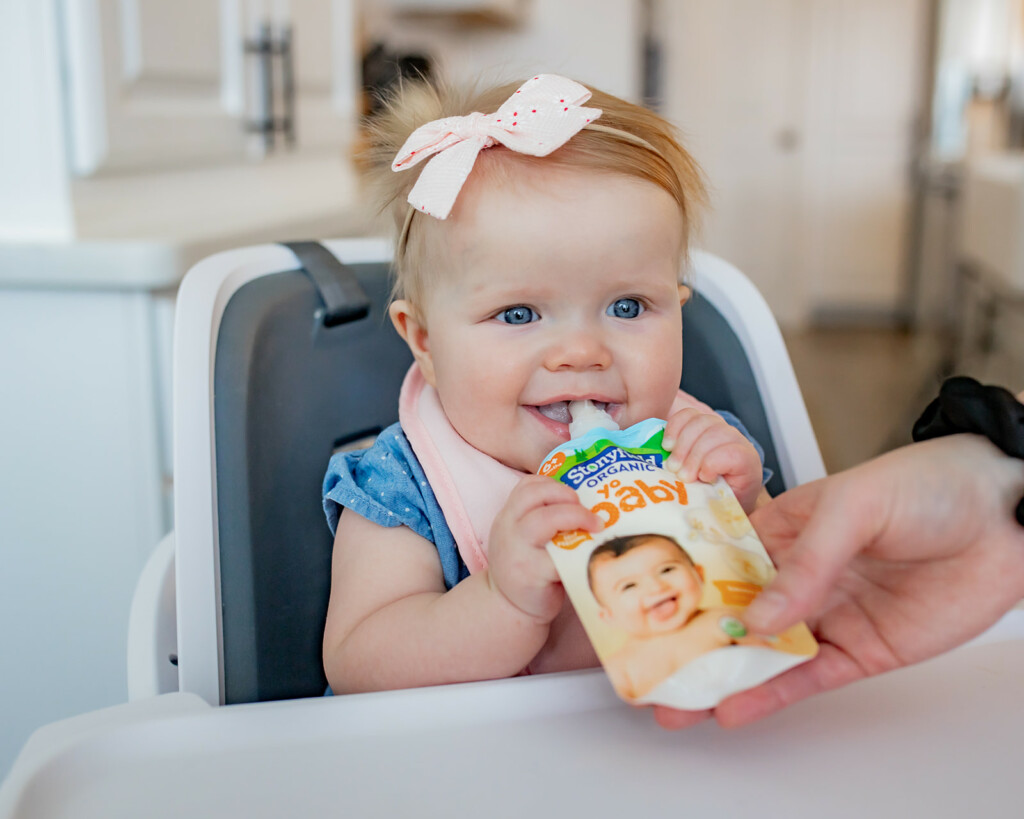 Baby girl eating Stonyfield Yobaby yogurt pouch in her high chair.