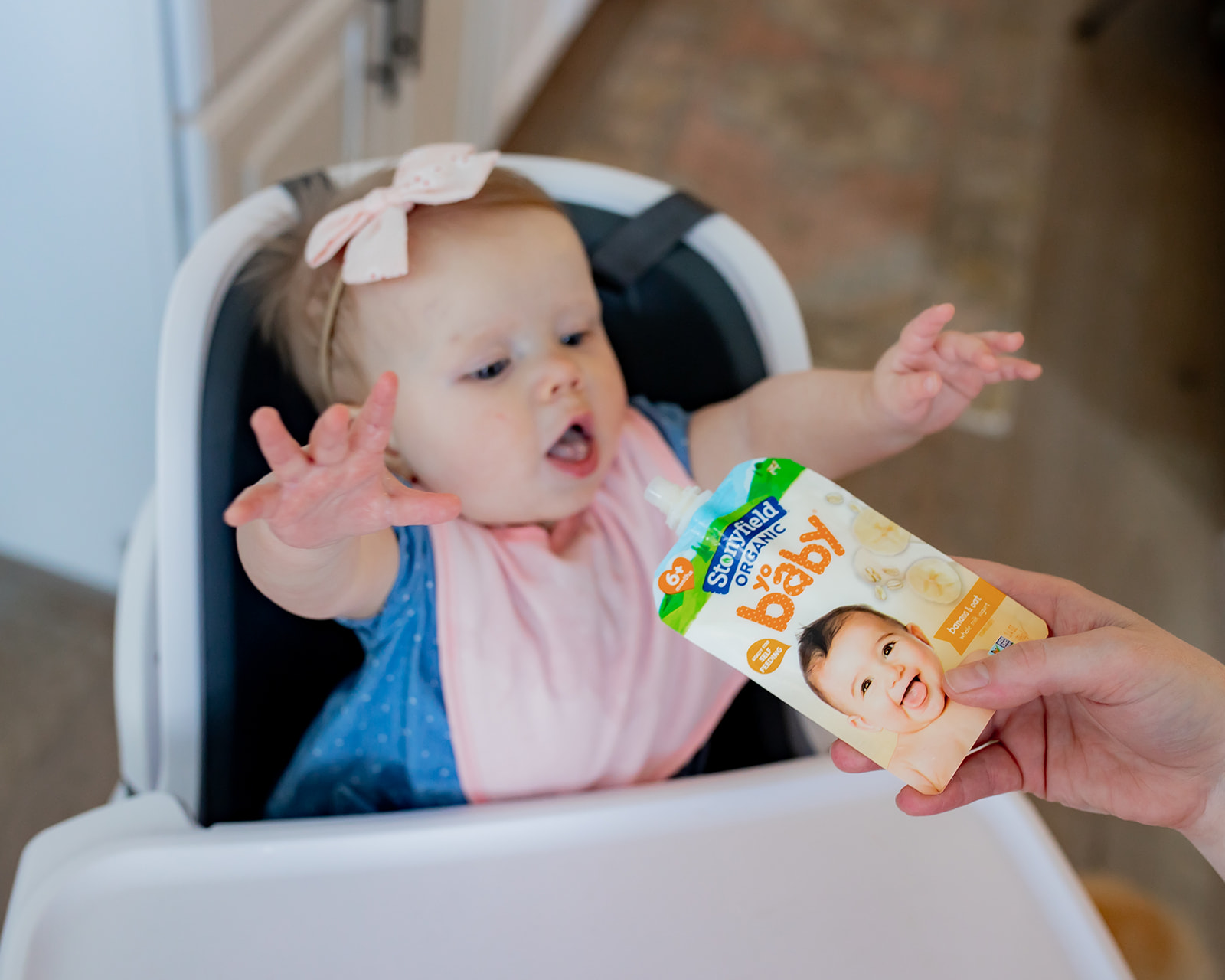 The baby girl reached out and tried to reach the Stonyfield pouch.