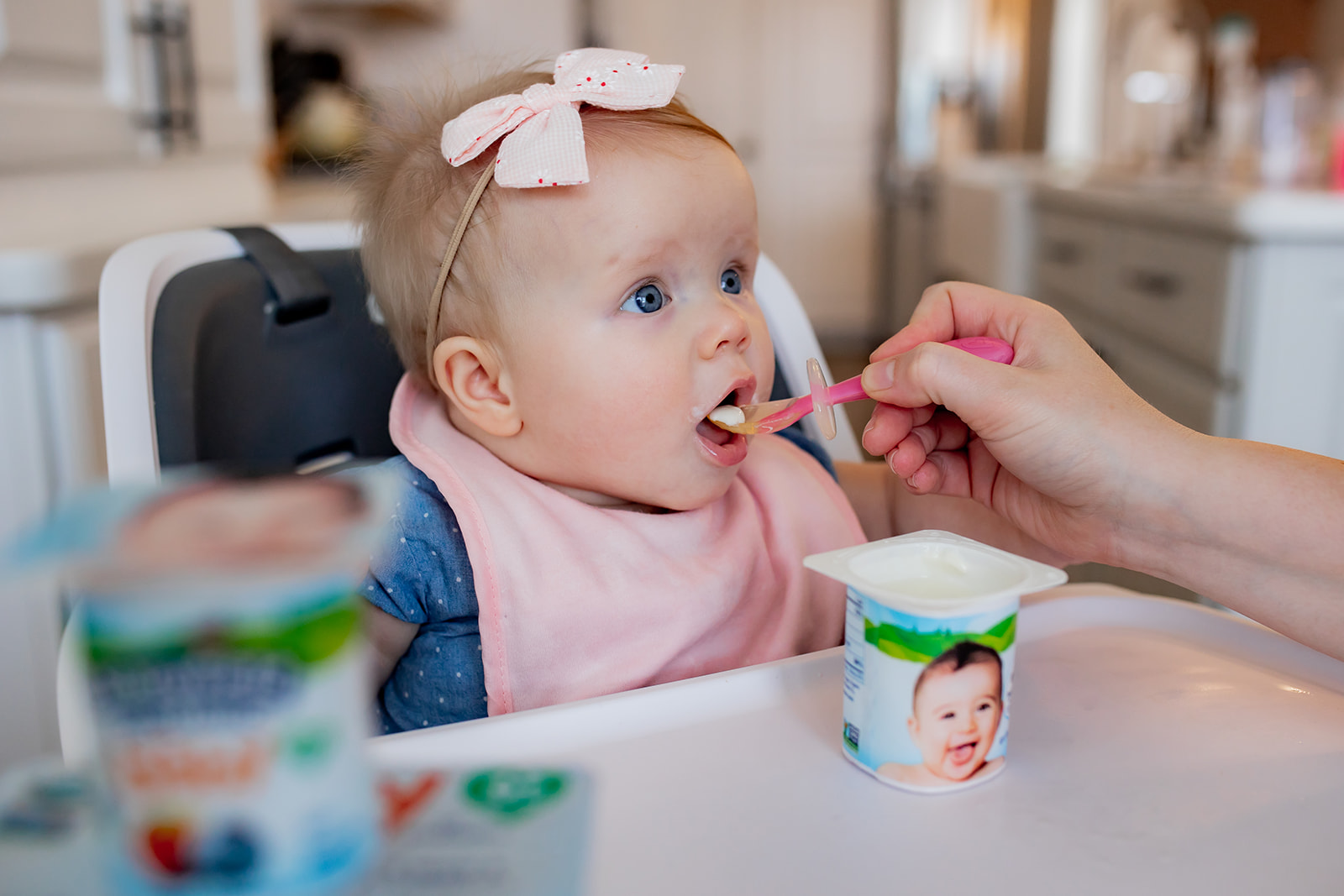 Little girl is eating yogurt with a spoon while sitting on her high chair.
