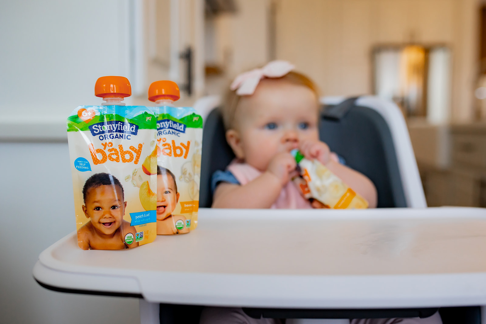 Stonyfield Yobaby pouch, in the background is a baby girl eating one of them.