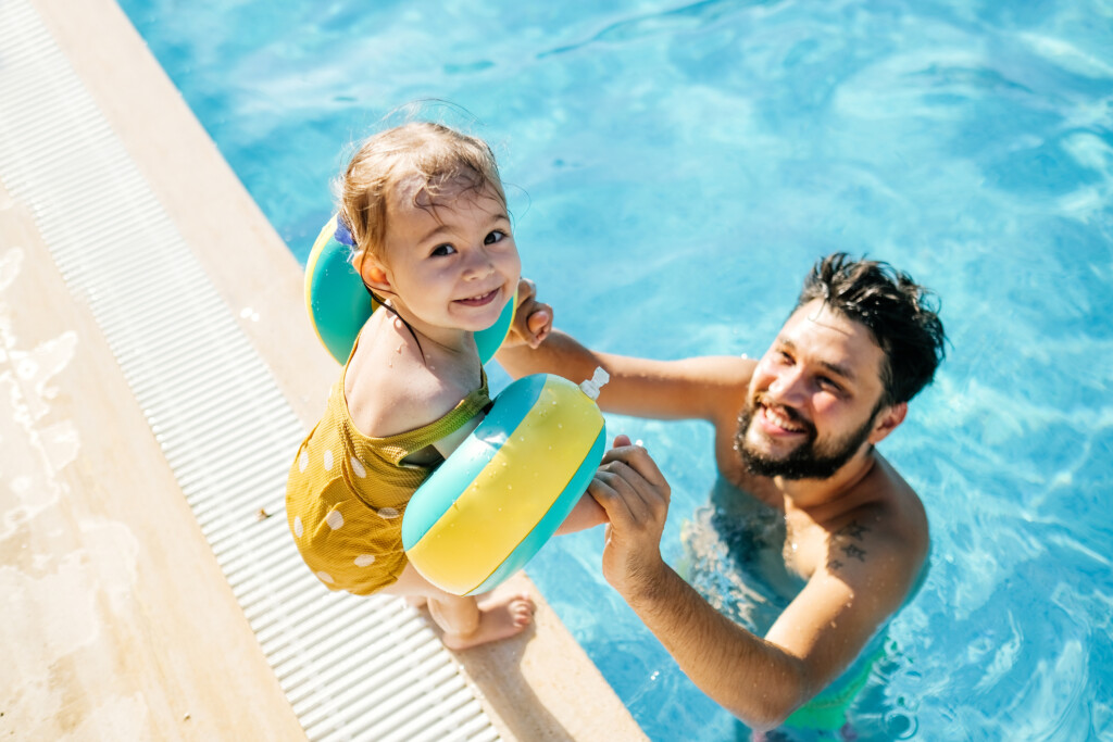 Cute little girl having fun with parents in pool.