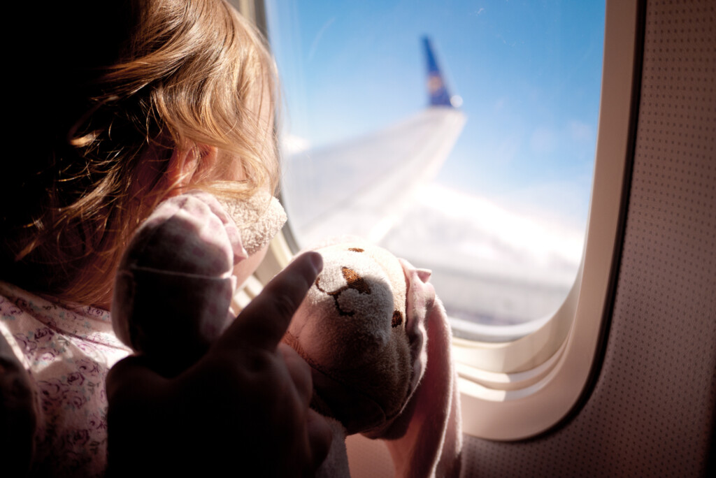 Baby girl sitting next to the airplane window looking out and holding her teddybear.