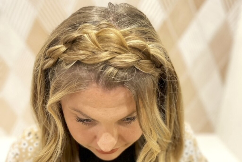 Woman looking down showing the top braided look on her head.