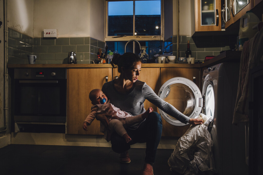 Young mother is holding her crying baby daughter on her hip while trying to load the washing machine.