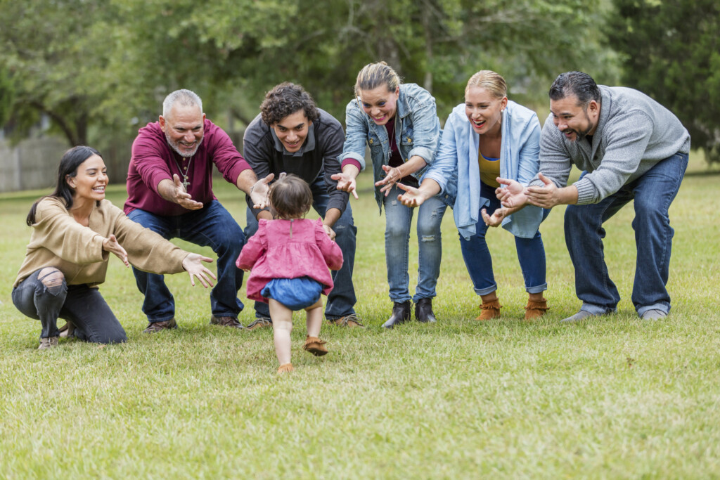 A multi-generation Hispanic family standing in the park together. A 16 month old baby girl is the center of attention. Her back is to the camera as she walks toward her family, all smiling with their arms open, reaching for her.