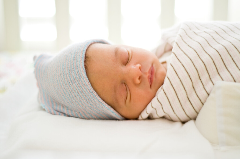 New-born baby sleeping on a bed wearing a blue hat