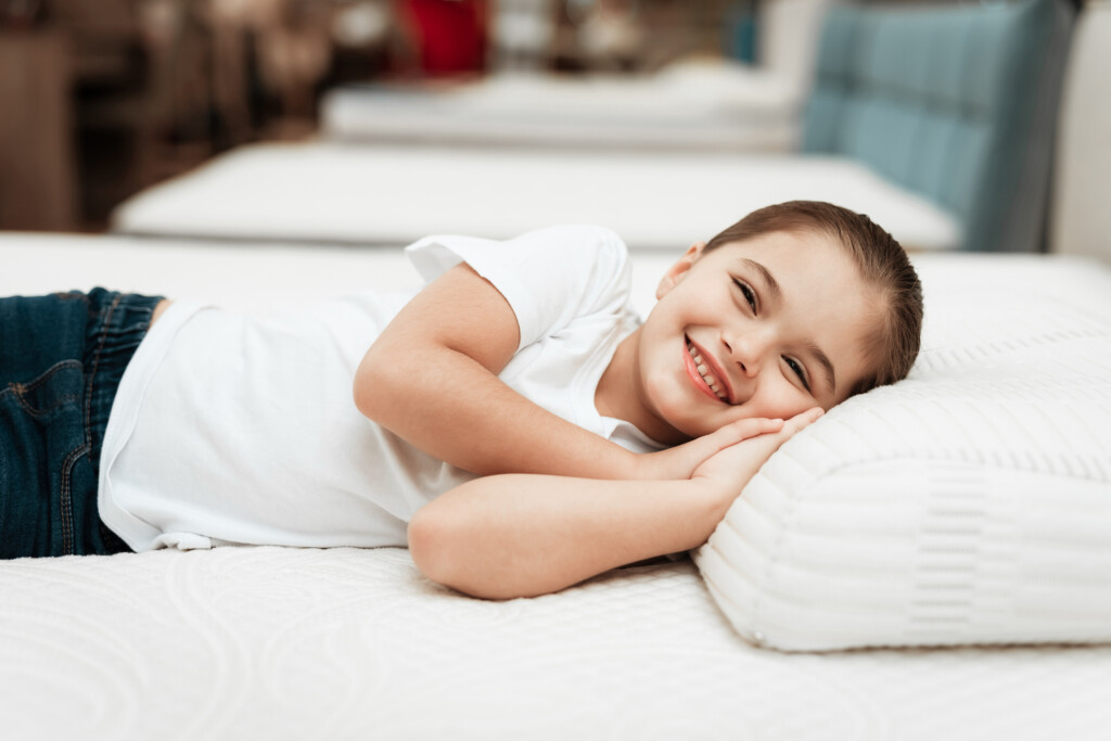 Smiling little girl lies on an orthopedic mattress in a furniture store.
