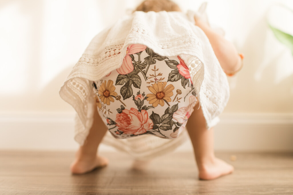 Toddler Crouched Down, Looking for Something While Wearing a Vintage Floral Modern Reusable Cloth Diaper and a White Shirt with a Neutral Wood Background in Bright Natural Light