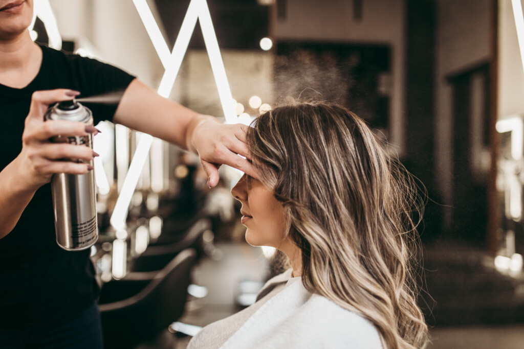 Beautiful brunette woman with long hair at the beauty salon getting a hair blowing.
