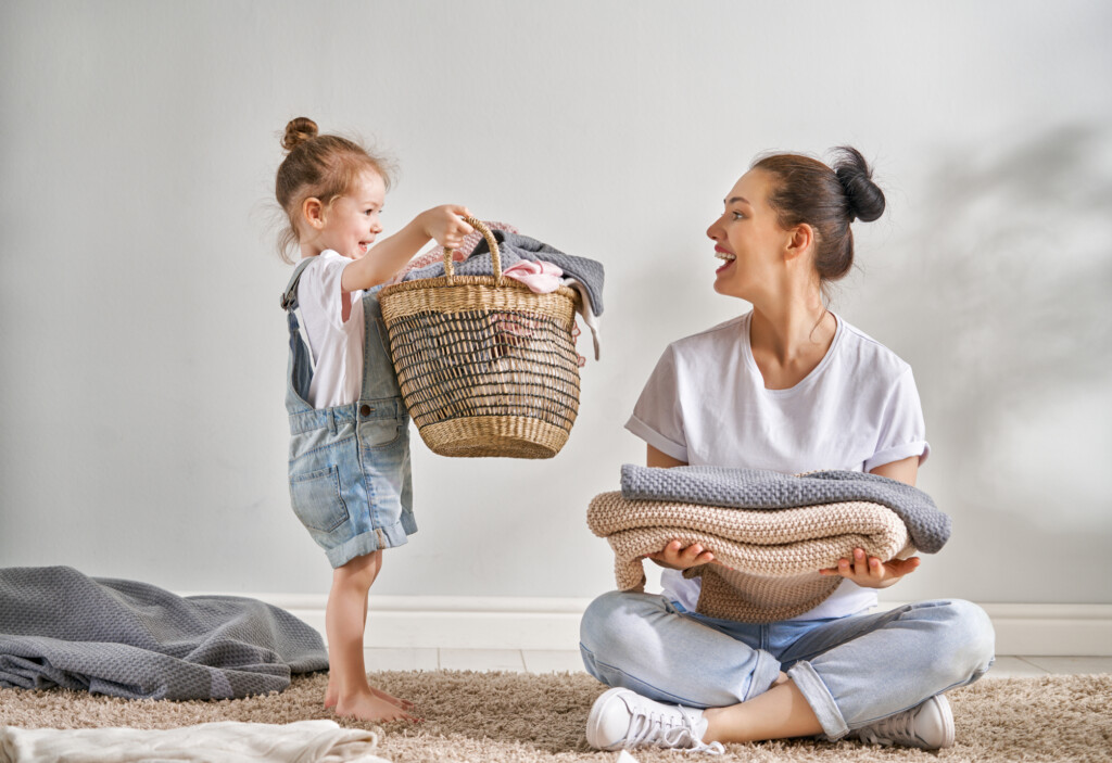 Beautiful young woman and child girl little helper are having fun and smiling while doing laundry at home.