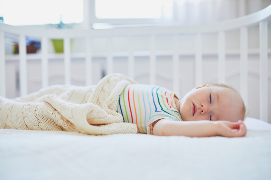 Adorable baby girl sleeping in co-sleeper crib attached to parents' bed. Little child having a day nap in cot. Infant kid in sunny nursery.
