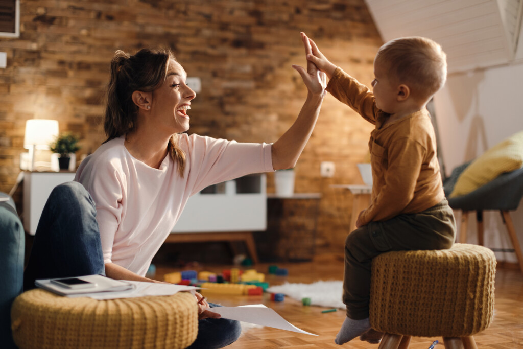 Playful mother and son giving high-five to each other and having fun at home. Focus is on mother.