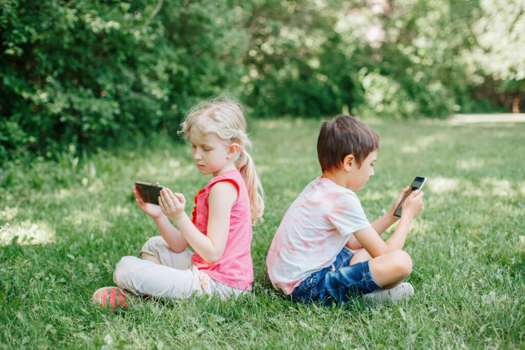 Boy and girl play games on smartphones outdoor. Kids digital gadget screen addiction. Children friends playing online sitting on grass in park.