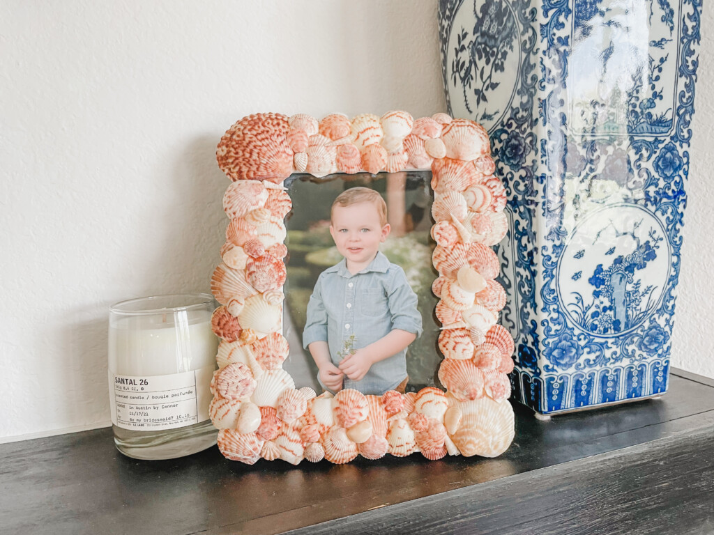 DIY shell frame on a mantel with a candle and vase.