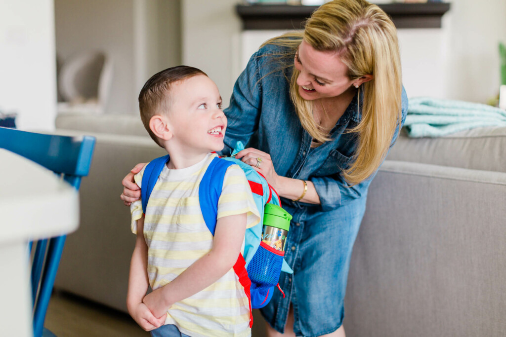 Mother helping her son put on his backpack to go to school.