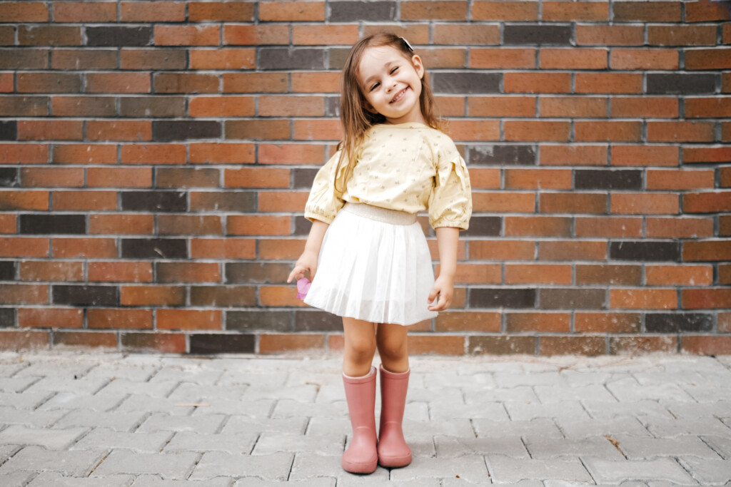 Cute little girl dressed up and posing in front of a brick wall.