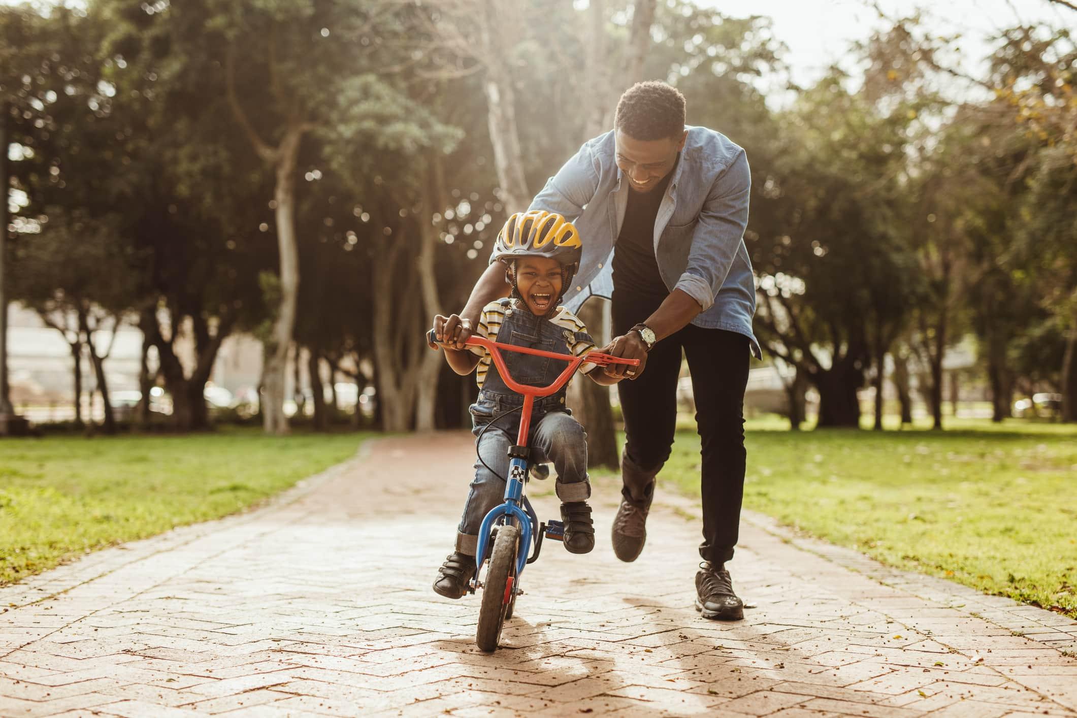 Jongen leert fietsen met zijn vader in het park.  Vader leert zijn zoon fietsen in het park.